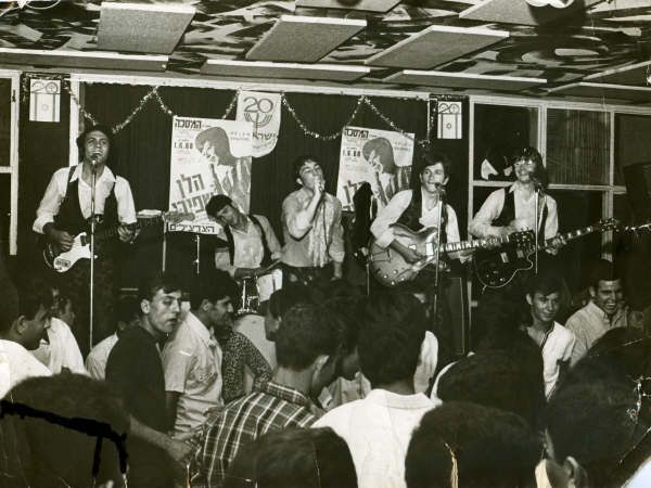 At the Masakha Club 1968. (L-R) Miki Gavrielov, Ami Trebich, Stan Solomon Haim Romano, Robb Huxley. Note...The almost entirely male audience, the poster advertizing Helen Shapiro, Haim Romano is using my Gibson 335 and I am using Churchills Guild guitar.