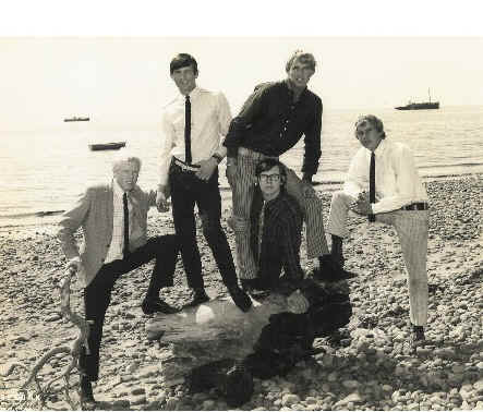 "The Tornados at Blackpool in 1966.  Photos taken on beach to publicise new record ""Is that a ship I hear"". Left to right: John Davies, Dave Watts, Pete Holder, Robb Huxley (front) and Roger Holder"